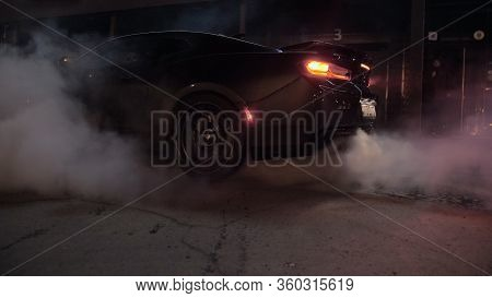 Tomsk, Russia - March 30, 2020: Chevrolet Camaro Zl1 The Exorcist Burns Rubber At Night Near Buildin