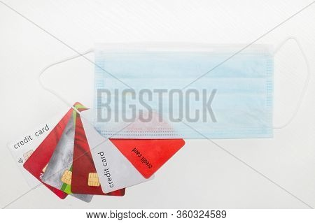 Outstanding Credit Cards And Medical Mask Laid Out On A White Table. Debt For Loans When A Person Is