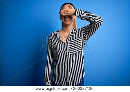 Beautiful blonde woman with blue eyes wearing striped shirt and glasses over blue background smiling and laughing with hand on face covering eyes for surprise. Blind concept.