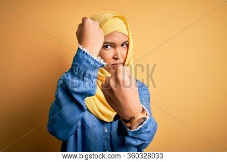 Young beautiful woman with curly hair wearing arab traditional hijab over yellow background Punching fist to fight, aggressive and angry attack, threat and violence