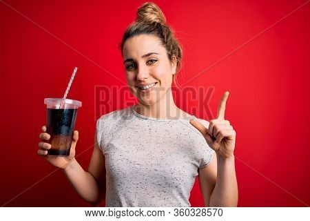 Beautiful blonde woman drinking cola fizzy beverage to refreshment over red background surprised with an idea or question pointing finger with happy face, number one