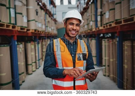Happy Male Factory Manager Using Digital Tablet In Warehouse While Standing Against Goods Shelf Look