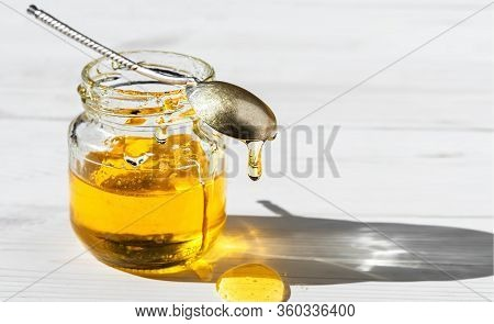 Organic Natural Honey In A Glass Jar On A White Wooden Background, Close-up. Vintage Spoon On An Ope