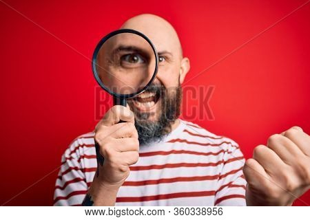Handsome detective bald man with beard using magnifying glass over red background screaming proud and celebrating victory and success very excited, cheering emotion