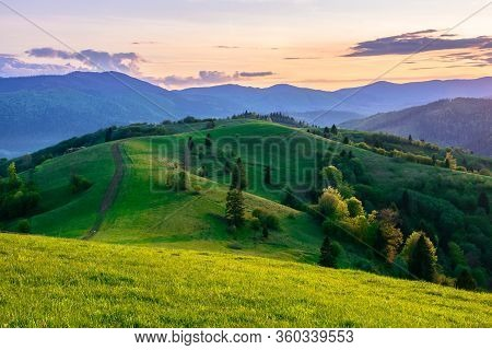 Mountainous Countryside In Springtime At Dusk. Path Uphill In To The Distance. Trees On The Rolling
