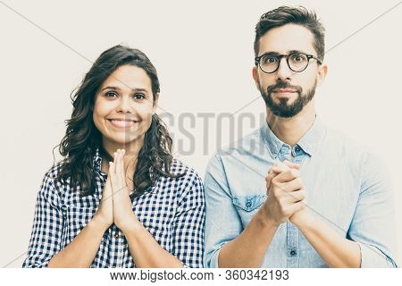 Excited Positive Couple Making Prayer Gesture, Asking For Luck, Looking At Camera. Young Woman In Ca