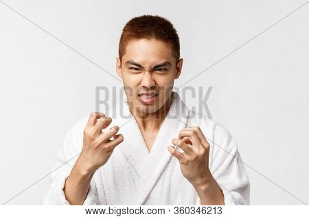 Beauty, Spa And Leisure Concept. Portrait Of Angry, Hateful Asian Man In Bathrobe Look With Hate And