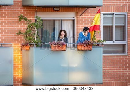 A couple applaud applaud at eight o'clock in balcony after Spain imposed a lockdown to slow down the spread of the coronavirus disease in Valencia, Spain on April 5, 2020.