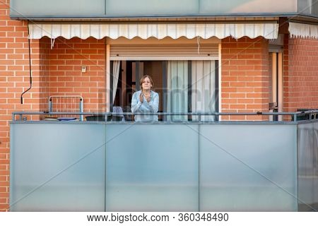 A woman applaud at eight o'clock in balcony after Spain imposed a lockdown to slow down the spread of the coronavirus disease in Valencia, Spain on April 5, 2020.