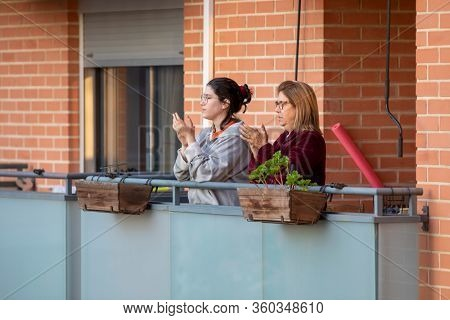 Mother and daughter applaud at eight o'clock in balcony after Spain imposed a lockdown to slow down the spread of the coronavirus disease in Valencia, Spain on April 5, 2020.