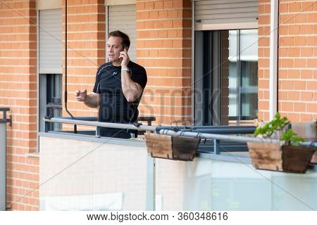 A man talking on the phone in balcony after Spain imposed a lockdown to slow down the spread of the coronavirus disease in Valencia, Spain on April 5, 2020.