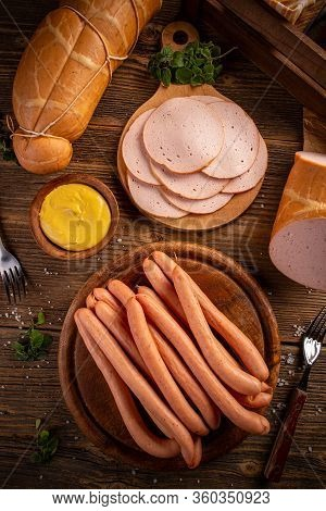 Top View Of Deli Meat Slices And Frankfurter Sausages Served With Mustard On Vintage Wooden Backgrou