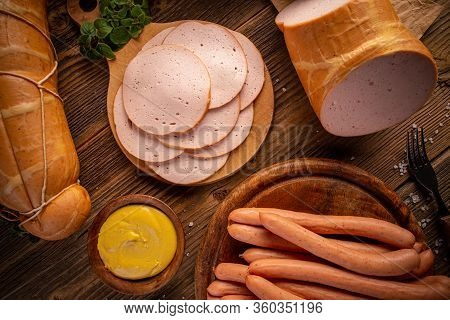 Composition Of Deli Meats And Wiener Sausages Served With Mustard On Wooden Cutting Board, Flat Lay