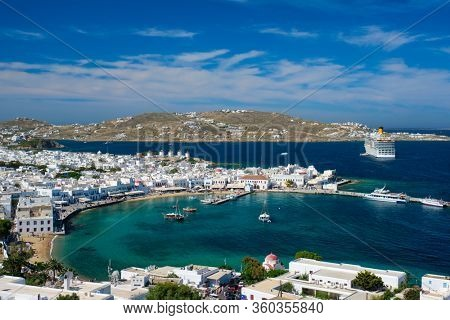 View of Mykonos town Greek tourist holiday vacation destination with famous windmills, and port with boats and yachts and cruise liner. Mykonos, Cyclades islands, Greece