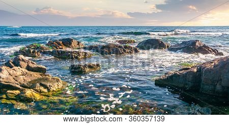 Rocky Shoreline Of The Sea In The Morning. Beautiful Scenery With Splashing Waves And Clouds On The