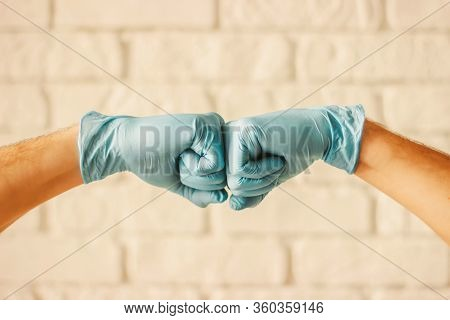 Two Men Bumping Hands In Blue Medical Gloves As Protection Against Coronavirus. Doctor Surgeons In B
