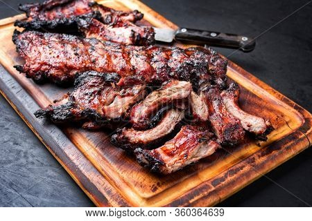 Barbecue pork spare loin ribs St Louis cut with hot honey chili marinade sliced and burnt as closeup on a wooden cutting board