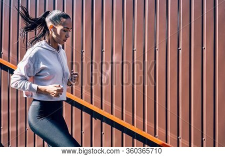 Fit Woman Running Down Stairs. Sport, Workout Concept