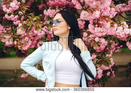 Young Beautiful Girl In Glasses. Spring Day. Beautiful Cherry Blossom Sakura In Spring Time. Spring