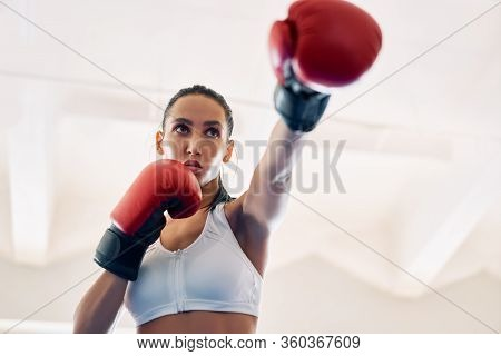 Female Boxer In Boxer Gloves Practicing Her Punches. Athletic Woman Making Direct Hit. Sport Concept