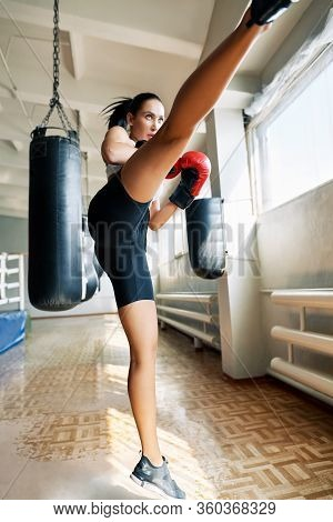 Female Boxer Doing High Kick In Gym. Young Woman Athlete Demonstrates Kickbox. Stretching And Balanc
