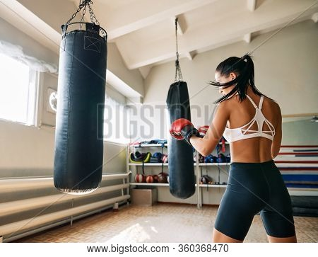 Back View Of Female Boxer Hitting A Huge Punching Bag At Fitness Gym. Woman Practicing Her Punches A