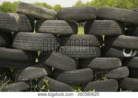 Old Tires Stacked To Form A Barricade Or Wall At A Fairground To Provide A Safety Feature For Partic