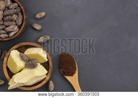 Cocoa Butter Or Cocoa Bean Solid Oil With Cacao Powder In Spoon And Raw Cocoa Beans In Wooden Bowl O