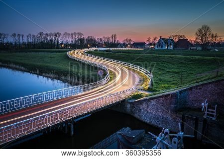 Curved Asphalt Country Road In Dutch Countryside With White Fence Leading Towards An Old Farmhouse I