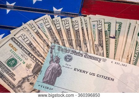 Stack Of 20 Dollar Bills With Illustrative Coronavirus Stimulus Payment Check On Usa Flag