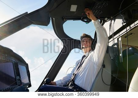 Male Pilot In Cockpit Of Helicopter Doing Pre Flight Check Before Take Off