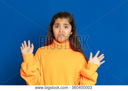 Adorable preteen girl with yellow jersey on a blue background