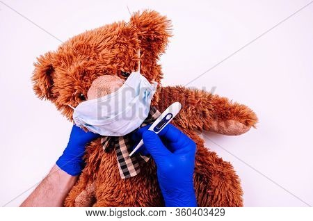 Man Hands In Blue Disposal Gloves Hold Thermometr And Medicine Face Mask On Teddy Bear