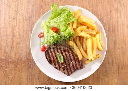 plate of beefsteak,french fries and lettuce