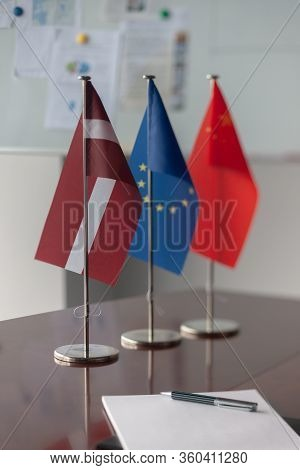 Latvian, Chinese And The Eu Flag Are On The Table With A Notebook And Pen Before Negotiations. Ea Wa