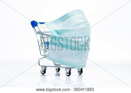 Shopping Cart With Protective Medical Mask Against Coronavirus. Safe And Online Shopping On Quaranti
