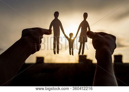 The Concept Of Support For A Young Family.hands Shows A Silhouette Of A Family On A Background Of Th