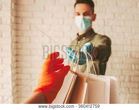 Delivery Man Courier In Protective Face Mask And Medical Gloves Giving Paper Bags To Customer. Girl