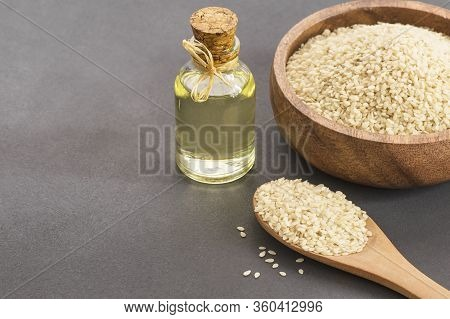 Glass Bottle Of Sesame Oil And Raw Sesame Seeds In Wooden Spoon And Bowl On Rustic Table. Uncooked S