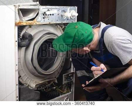 Repair Of Washing Machines, Repair Of Large Household Appliances. A Technician Examines An Old Broke