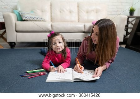 Beautiful Little Girl And Her Mother Lying On The Carpet Floor And Doing Homeschool Together
