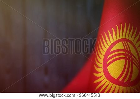 Kyrgyzstan Hanging Flag For Honour Of Veterans Day Or Memorial Day On Blue Blurred Natural Wood Wall