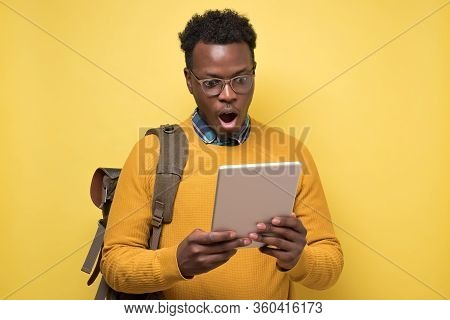 Happy African American College Student In Glasses Holding Tablet On Yellow Wall.