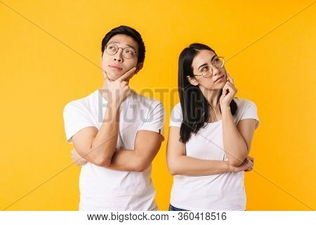 Image of serious multinational man and woman thinking and looking aside isolated over yellow background