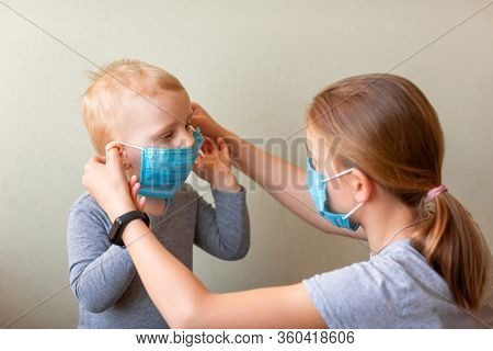 Teenage Girl Helping To His Baby Brother To Wear A Medical Mask