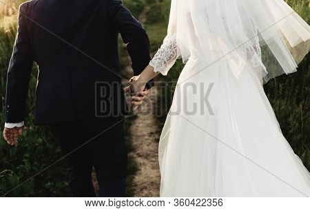 Bride And Groom Run Across The Field At Sunset Wedding Day,couple In Love Holding Hands And Running