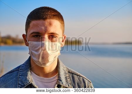 Young Boy Wearing Protective Surgical Face Mask To Prevent Coronavirus On The Lake Background. Close
