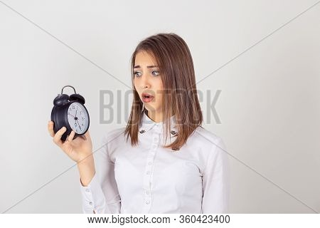 Closeup Headshot Young Business Woman With Alarm Clock In Hand Isolated White Grey Wall Background.
