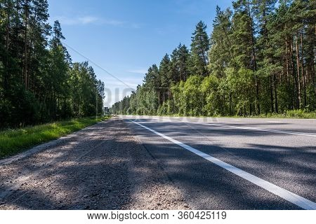 Empty Highway, Two Lane Road And The Forest. Asphalt Road Travel Concept.