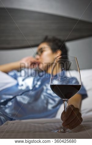 A Distraught Woman Wearing Satin Pajamas Sits In Bed With A Glass Of Wine